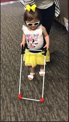 Three year old walking wearing belt cane