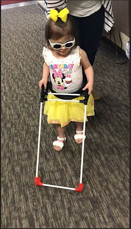 Three-year-old girl, blind walking independently dressed in bright matching skirt, shirt, shoes and hair ribbon. She is also wearing her belt cane, one hand on either side - working it.