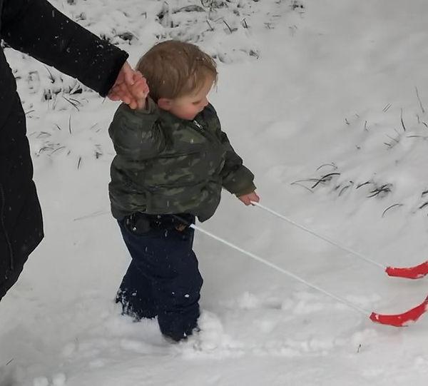 two-year-old boy blind wearing belt cane walking through fresh snow.