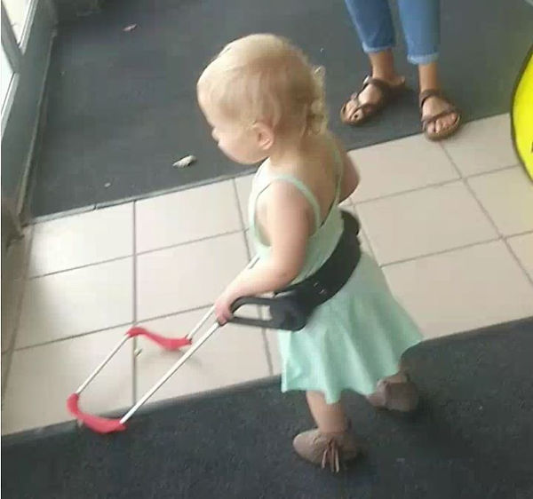 one-year-old girl who is blind stands tall, both hands on her belt cane walking indeendently.