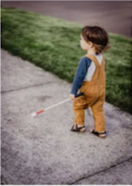 The cane is in the left hand, the cane tip is on the left outside the path of the child.