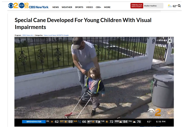 CBS-NY logo and website banner, title Special Cane Developed for Young Children with Visual Impairments, photo shows dad holding one hand and his other arm at his side, the belt cane in front as they walk on the sidewalk in bright sunlight