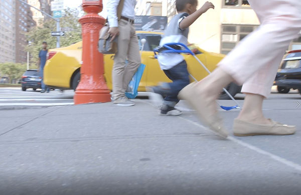 side view of four-year-old boy running on NYC sidewalk wearing his belt cane