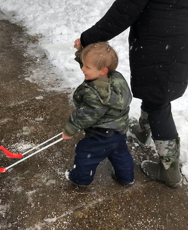 two-year-old boy, blind wears belt cane on sidewalk, snowy day, one hand on cane, one holding parent's hand.