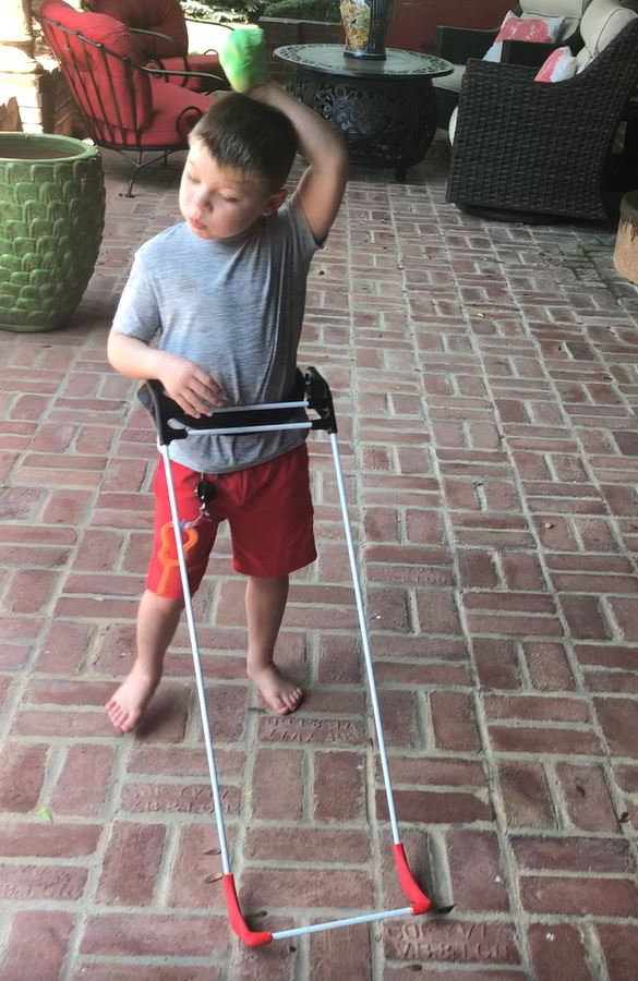 five-year-old boy stands on his brick patio wearing his belt cane. One hand rests on the cane, the other is up in the air. He is taking a step.