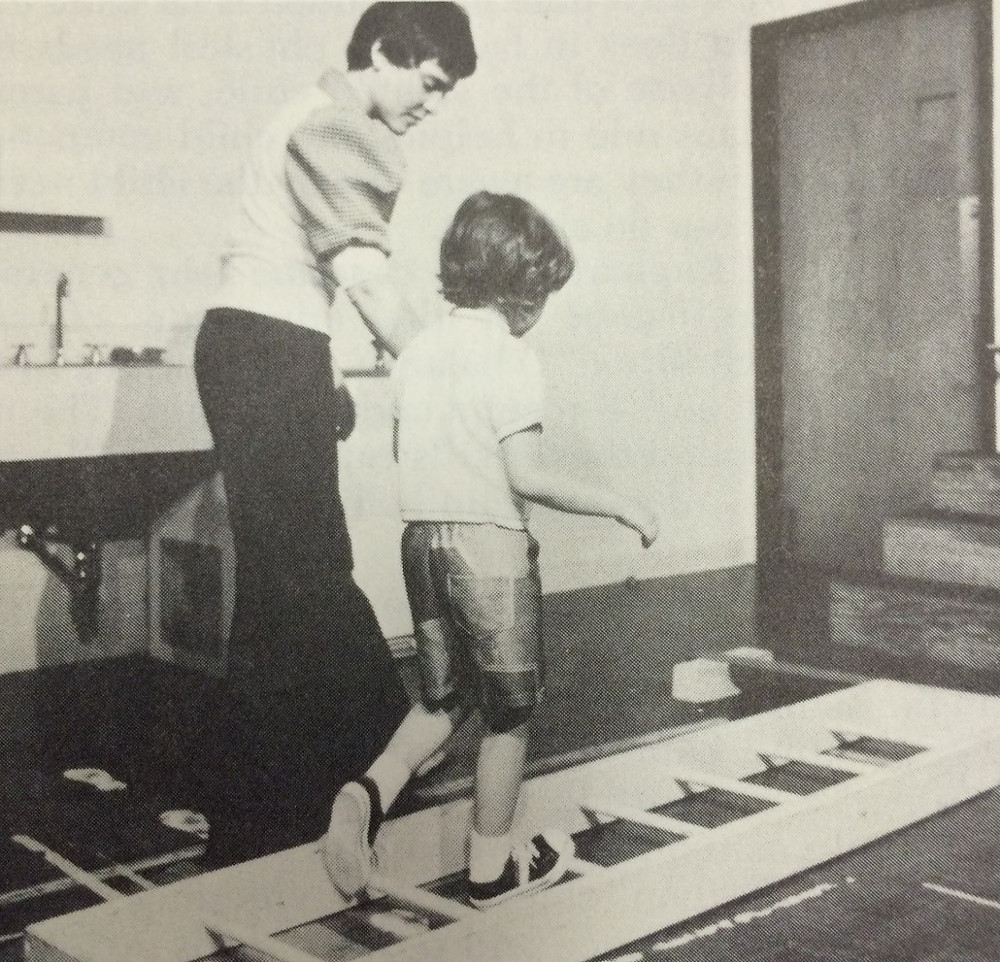 A child holds the hand of an adult and is stepping, his back toe is catching on the ladder rung, his right toe is on top of another ladder rung.