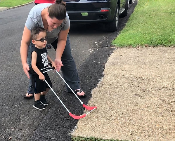 2-year-old visually impaired boy wearing belt cane is having an O&M lesson on street crossing