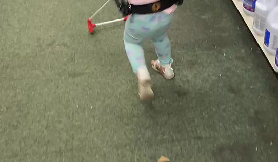 Kenedi walks about as her belt cane stops her from running into obstacles.