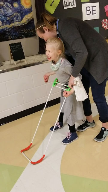 seven year old with impaired hands, walks wearing her belt cane, big smile, an adult is behind her with one hand on the belt.