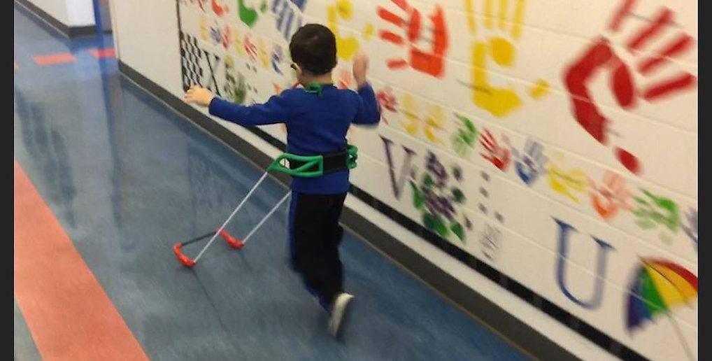 three-year-old boy visually impaired wears belt cane running down school hallway