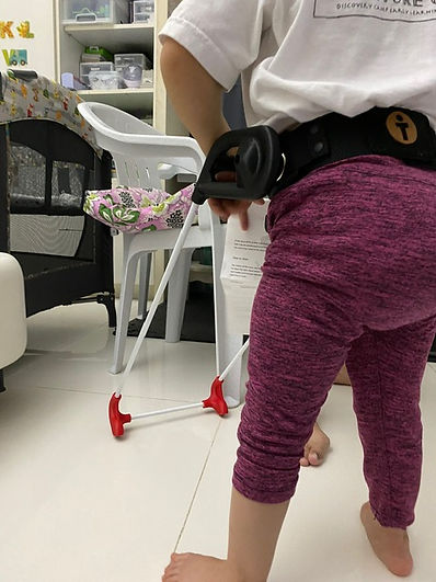 little one-year-old girl locates a chair with her belt cane base. Both hands on the cane.