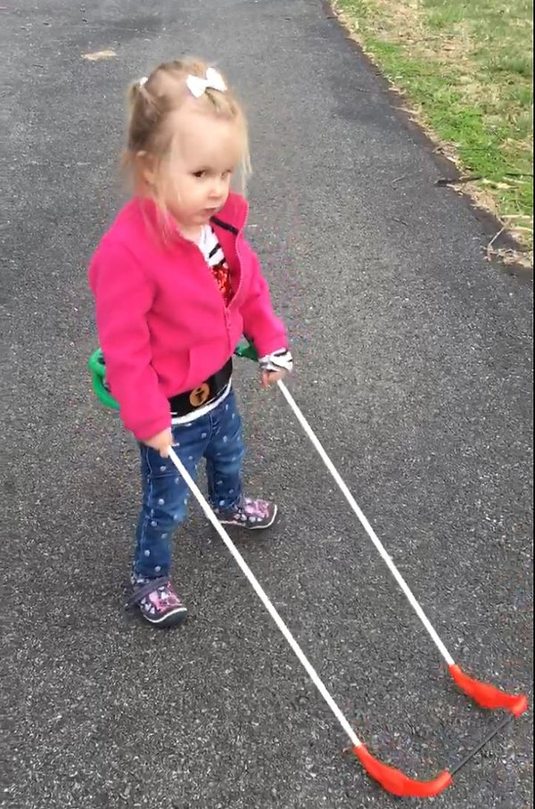two-year-old girl who is blind wears belt cane, both hands holding cane shafts