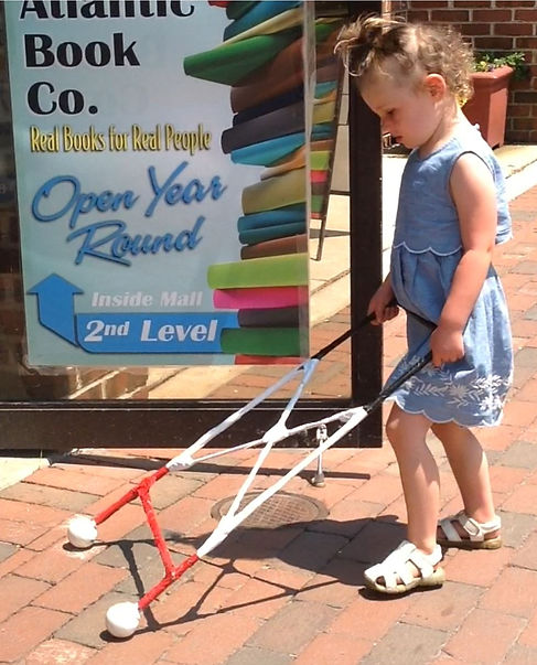 three-year-old walks into a store using a rectangular cane