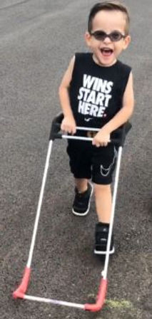 "two year old with tunnel vision, big smile walking down the street independently, shirt reads ""wins start here"" wearing belt cane both hands tightly grasping the cane frame."