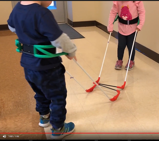 Two children wearing belt canes meet in a hallway when their canes contact each other