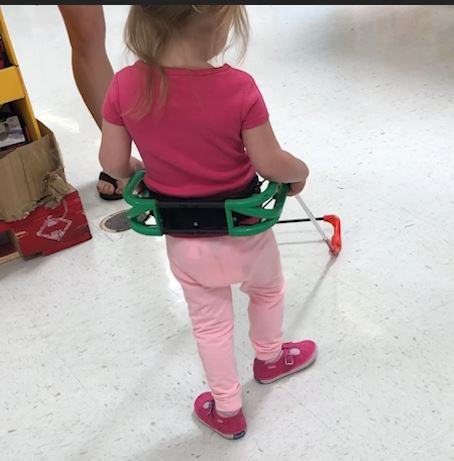 two-year-old girl who is blind walks with belt cane both hands grasping the cane