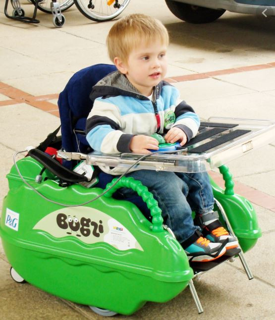 A three year old boy in a bright green enclosed wheelchair, he sits two hands operate a simple on/off switch.