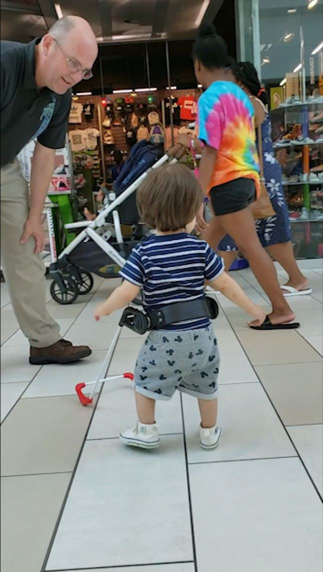 A 20 month boy walks independently, he is blind and wearing a belt cane.