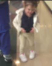Avery girl, caucasian, walks, feet toe in, hands clenched, zipper sweater, blue shirt, tan pants tennis shoes