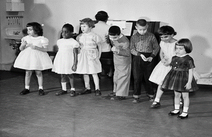 black and white photo: Seven preschool children who are blind in a line, their back to the piano being played by and adult woman her back is to the camera.