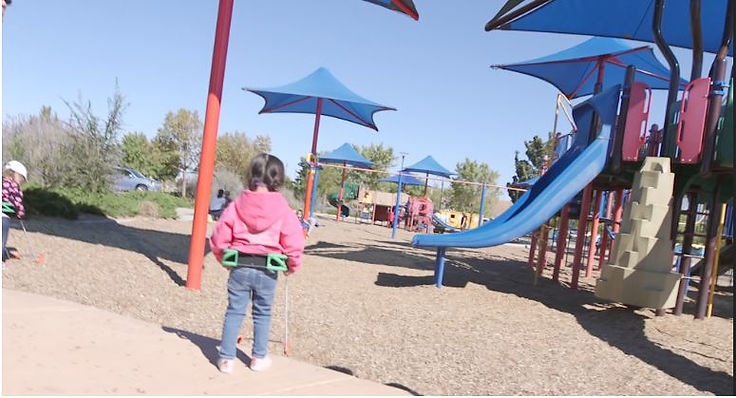 three-year-old girl back to camera appears to be entering a playground her belt cane has fallen off the sidewalk to show exactly where she needs to step down.