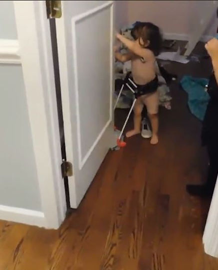 Two year old blind girl, is closing the door, hands reaching across her body, cane frame base i contact with door, not in the way.