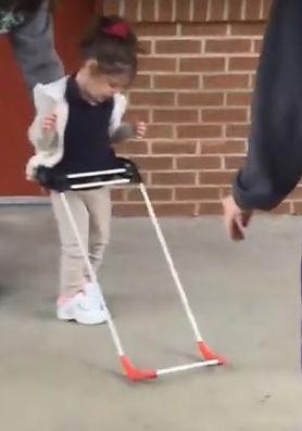 Three year old girl walking wearing belt cane