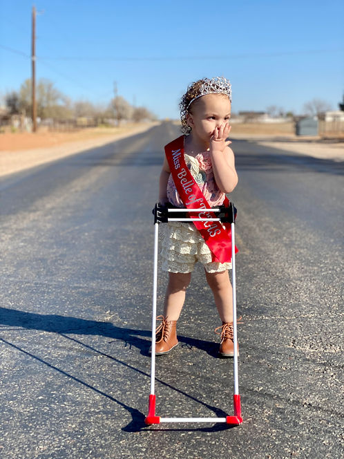 """two year old girl who is blind due to optic nerve hypoplasia stands in the middle of a paved road that is deserted on a sunny day. She wears a crown, a red sash that reads """"Miss Belle of Texas"""" and her pediatric belt cane. She is blowing a kiss the the viewer."""