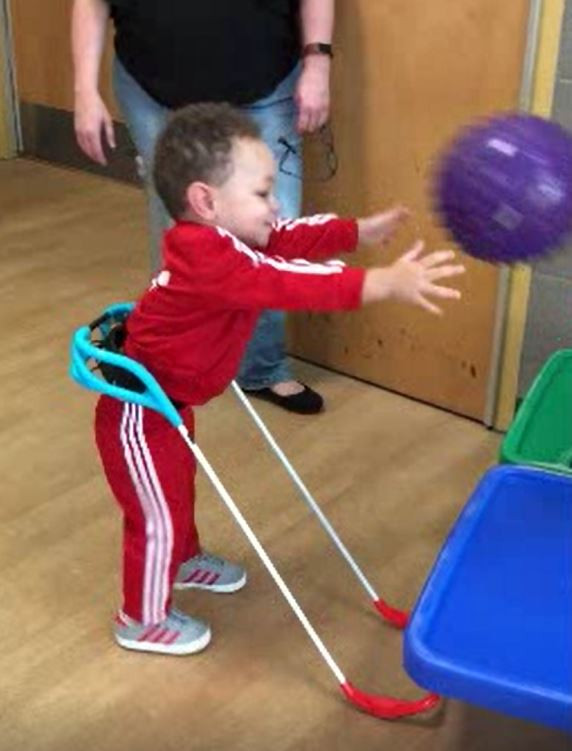 Two year old wearing his cane is throwing a purple ball. He is in a school gym wearing a track suit.