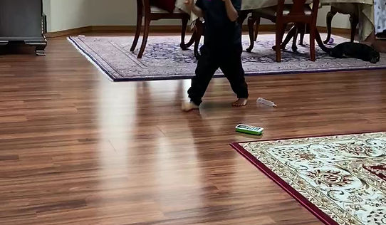 Kenedi walks three steps from her dad (seated on floor) to her mom (seated on floor), returns to her dad, falls and he helps her turn around and she walks back to her mom