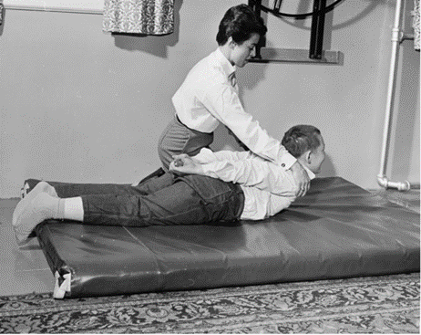 black and white photo of a child lying on his belly on a thick mat. His hands are clasped behind him, the PT kneels beside him and is pulling his shoulders away from the floor.
