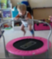 Matias, boy, caucasian blonde hair, t-shirt and diaper holds onto a bar on the mini-tramp mid-jump
