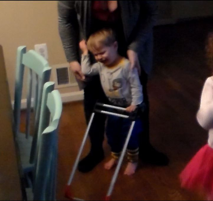 Matias is crying, he is standing wearing his belt cane, one arm grasps his mother, the other is pushing down on the cane frame.