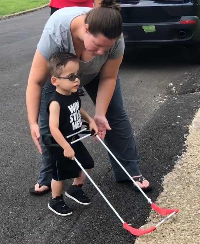 Two year old with tunnel vision is seen on an O&M lesson. He is traversing a city street wearing his cane. The cane has a black belt, white rectangular frame and red base with ball bearings.