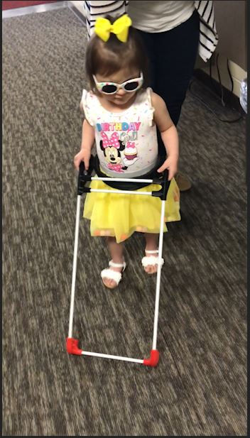 three year old girl walks down school hallway wearing her belt cane. both hands are on the cane frame.
