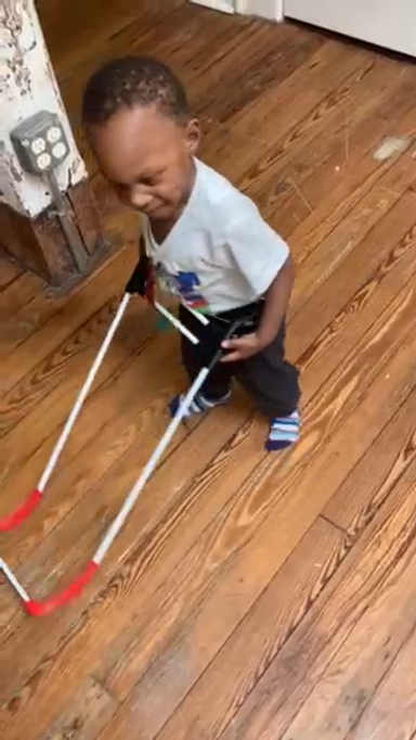 one year old boy with cortical visual impairment wears his pediatric belt cane at home