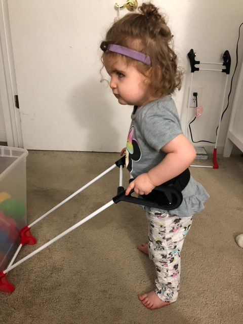 two year old girl with CHARGE syndrome wears her cane standing up in her room.