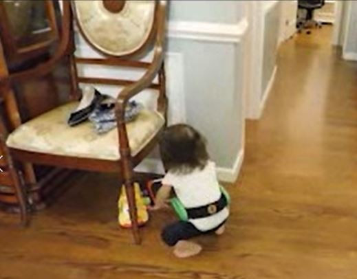 Charna is kneeling, her left hand is reaching for the toy, the belt frame is pushing against the wall.