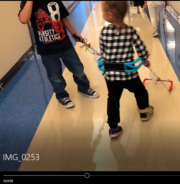 Girl and boy in school hallway, both are visually impaired one using a rod cane, the other wearing her belt cane.