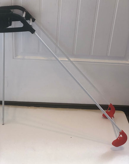 side view of tight spaces cane, black 3D printed top, white carbonfiber cane rods extend to red 3D printed tips, rounded to reduce catching on furniture legs