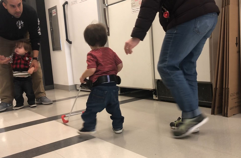 Twin who is blind is walking wearing his cane, no adult holds or helps him, mother walks behind him. His twin brother being held back by his father.