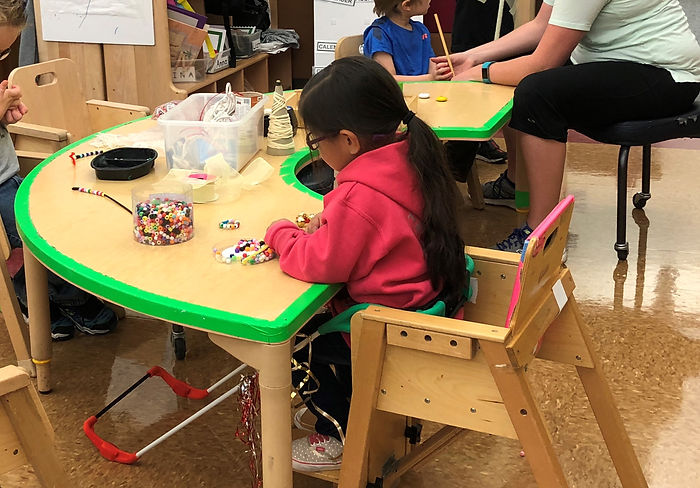three-year-old visually impaired girl sitting at her school desk wearing a belt cane