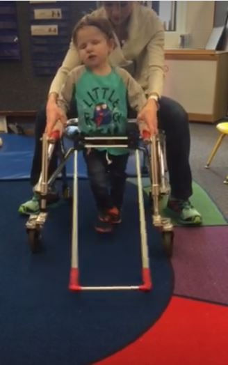 three-year-old boy, blind wearing belt cane and using gait trainer to walk