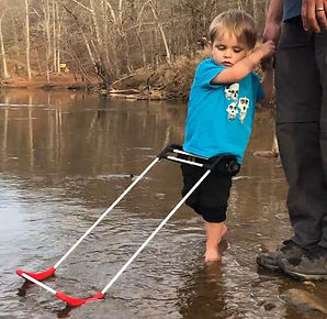Two year old boy wading in creek wearing belt cane