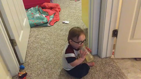 sits drinking his bottle, trys to stand up, begins crawling