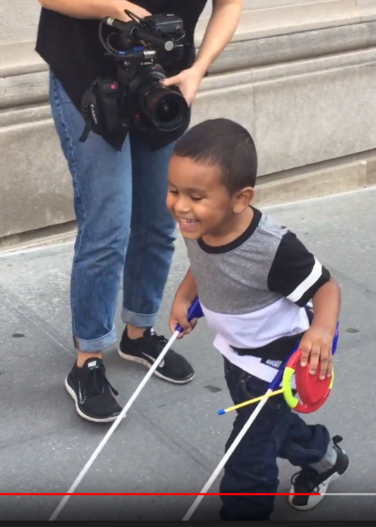 Boy smiling, running, one hand holds cane the other the control for remote control toy