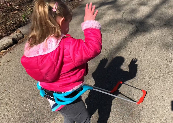 three year old girl is wearing her belt cane, she is holding her hands up to make a fun shadow on the ground