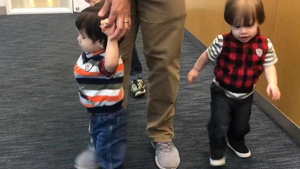Twin who is blind being assisted by his dad, both hands held above his head, sighted twin walks on his own, arms down.