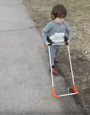 three year old walking on sidewalk, both hands holding cane.