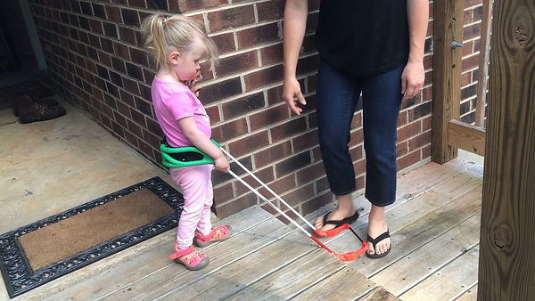 Two year old girl who is blind wearing a belt cane is walking toward a down step, the belt cane frame has fallen off the step indicating the exact location of the step down.